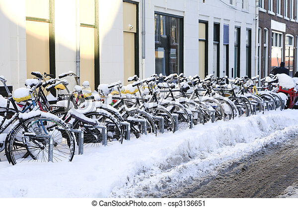 A row of snowcovered bikes - csp3136651