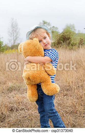 Cute little girl hugging a big Teddy bear