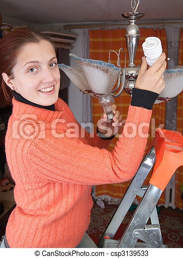 Girl changes innovation bulb - csp3139533