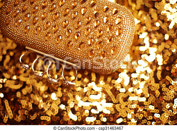 Fashion golden womens accessory. Luxurypurse on yellow sequins sparkling sequined textile.