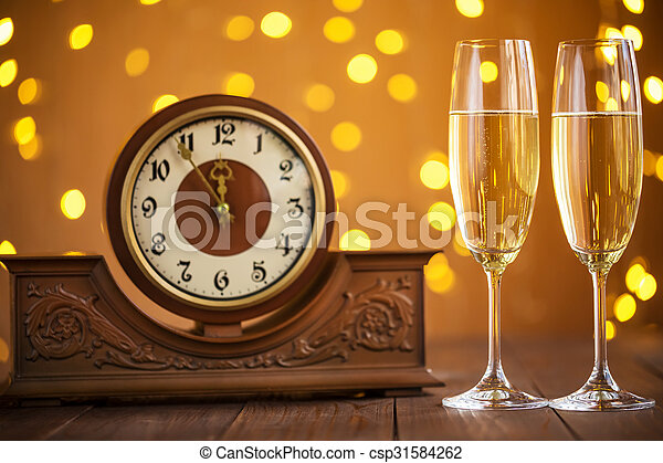 Christmas card. Glasses of champagne on New Year\'s Eve on the stand an ancient clock