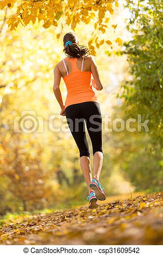 Female fitness model training outside and running.