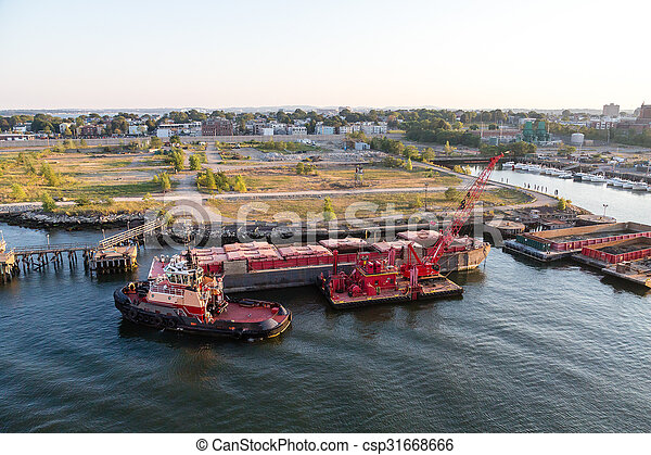 A tugboat pushing a heavy barge at a commercial pier