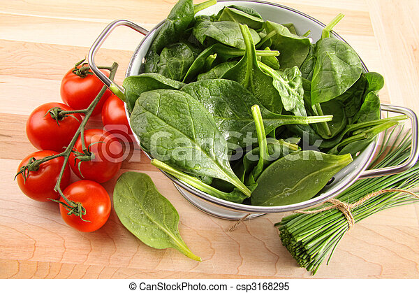 Strainer with spinach leaves and tomatoes - csp3168295