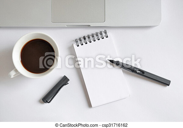 Coffee cup, spiral notebook, computer keyboard, and pen on white background