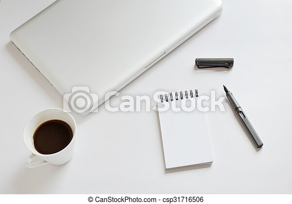 Coffee cup, spiral notebook, laptop, and pen on white background