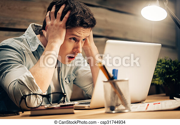 Feeling sick and tired. Frustrated young man holding head in hands and looking at laptop while working late at his working place