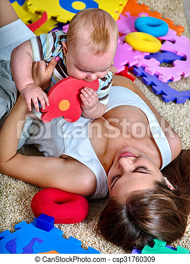 Kid baby boy with mother plying puzzle toy on floor.