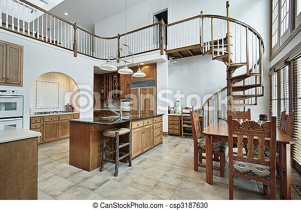 Large kitchen with spiral stairway to second floor - csp3187630