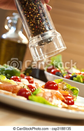 A pepper mill grinding pepper onto a seafood salad of smoked salmon and shrimp or prawns, shot in golden light with olive oil and balsamic vinegar out of focus in the background. - csp3188135