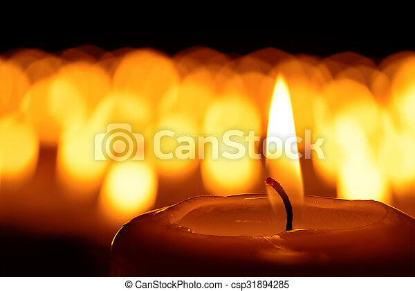 Candle in front of many defocused candleflames creating a spiritual atmosphere and in remembrance of loved ones