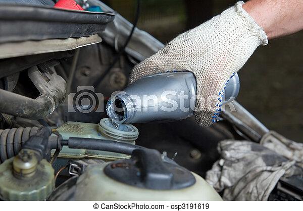 The mechanic fills in a brake liquid - csp3191619