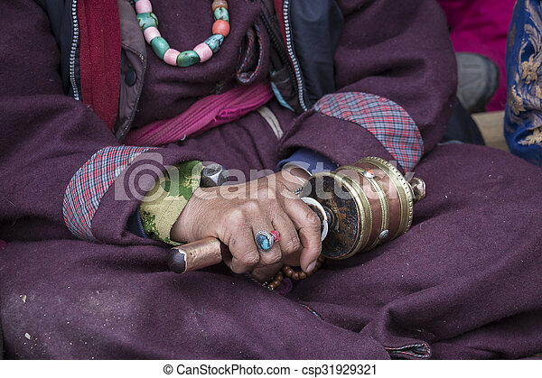 Old Tibetan woman holding buddhist prayer wheel in Lamayuru Gompa, , Ladakh, India. Hand and prayer wheel, close up