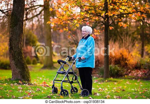 Senior lady with a walker in autumn park