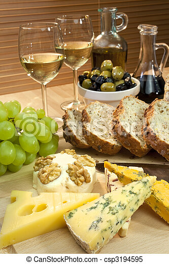 A platter of Mediterranean food including cheese, grapes, white wine, bread, olives, olive oil and balsamic vinegar. Shot in beautiful warm light with the focus on the cheese in the foreground. - csp3194595