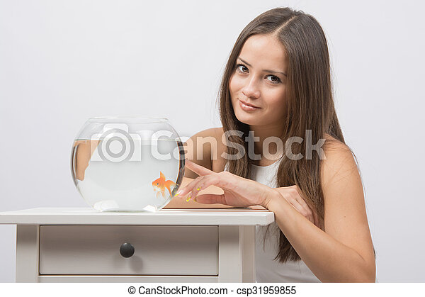 The girl points a finger at aquarium with goldfish
