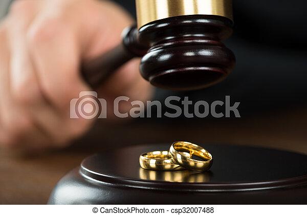 Divorce Judge Hitting Gavel On Golden Rings At Desk