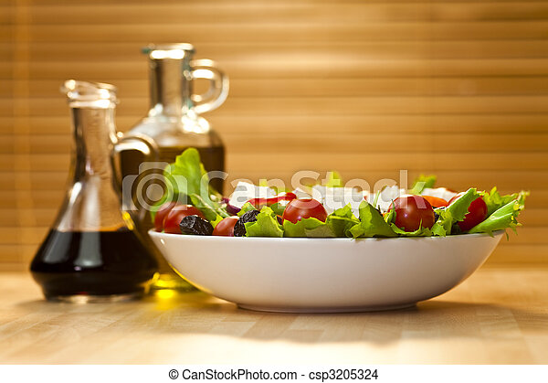 Tomato, mozzarella, or feta cheese salad with black olives, olive oil and balsamic vinegar dressing in bottles out of focus in the background, shot in golden sunshine - csp3205324