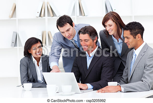 Multi-cultural business team looking at a laptop - csp3205992