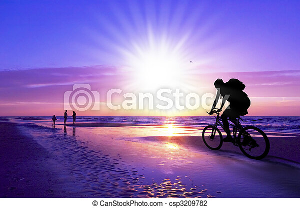 mountain biker on beach and sunset - csp3209782