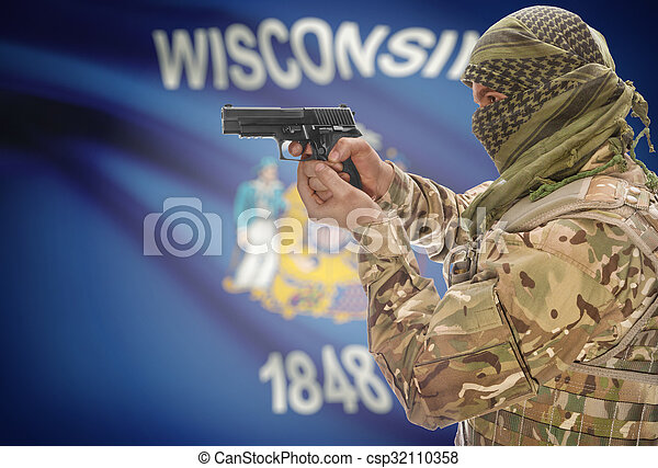 Male in muslim keffiyeh with gun in hand and flag on background - Wisconsin - csp32110358