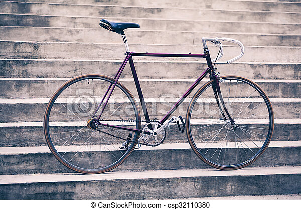 Road bicycle, fixed gear bike on city concrete street. Urban industrial cycling, bike on city stairs steps bicycle closeup, vintage old retro bike, cycling or ecology commuting. Industrial concept.