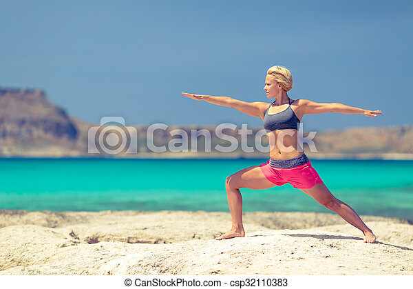 Yoga pose, fit woman stretch and exercise on a beach and mountains. Girl doing yoga Virabhadrasana pose. Motivation exercising and inspirational beautiful landscape. Healthy lifestyle outdoors in nature, fitness concept.