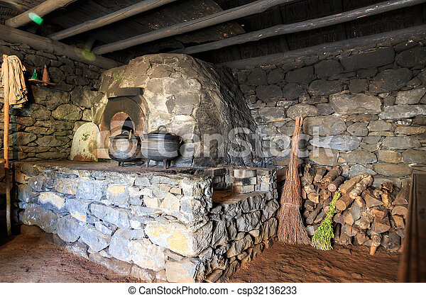 Ancient kitchen interior with furnace, pots and lumber