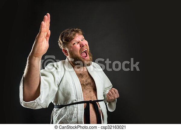 Mad bearded strong karate fighter in white kimono over grey