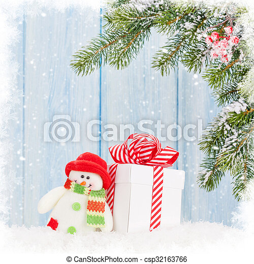 Christmas gift box, snowman toy and fir tree branch with snow