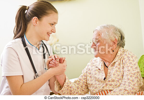 A young doctor / nurse visiting an elderly sick woman socialising - talking - with her, holding her hands. - csp3220000
