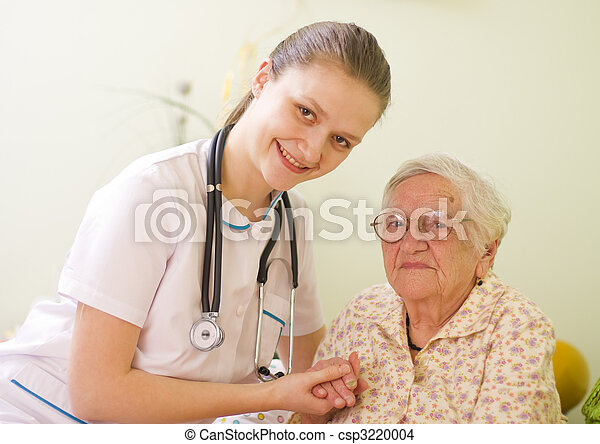 A young doctor / nurse visiting an elderly sick woman holding her hands with caring attitude. - csp3220004