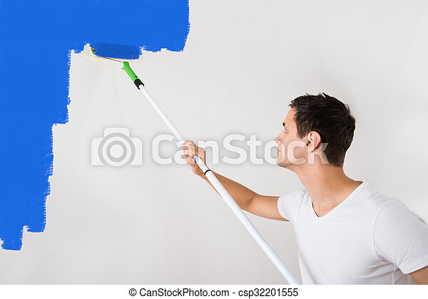 Man Painting Wall With Blue Paint Roller