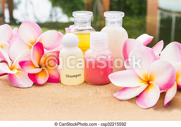 Mini set of bubble bath and shower gel on rock tile floor beside the pool decorated with fragrant beautiful flower