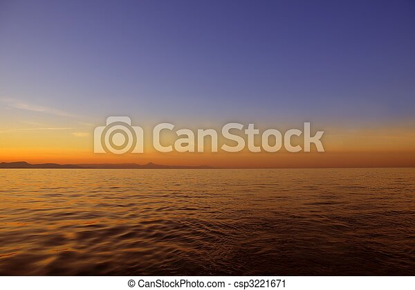 Beautiful sunset sunrise over blue sea ocean red  sky - csp3221671