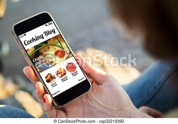 woman sitting in the street holding her smartphone with cooking blog on screen
