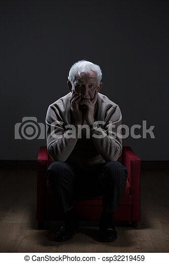 Worried elder man sitting alone in empty room