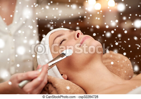 people, beauty, spa, cosmetology and skincare concept - close up of beautiful young woman lying with closed eyes and beautician hand applying facial mask by brush in spa salon with snow effect