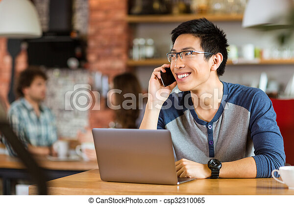 Positive asian man using laptop and talking on cellphone - csp32310065