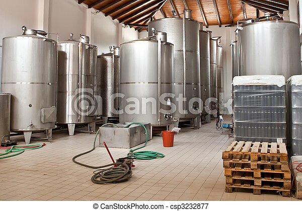 Wine Fermenting in huge vats in a wine cellar - csp3232877