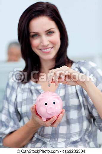 Charismatic businesswoman saving money in a piggy-bank - csp3233304