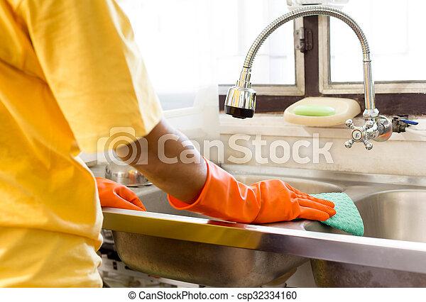 Hand with orange glove cleaning Kitchen sink