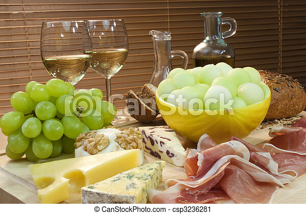 A platter of Mediterranean food including cheese, grapes, white wine, bread, Parma ham, melon, olive oil and balsamic vinegar. Shot in beautiful warm light. - csp3236281