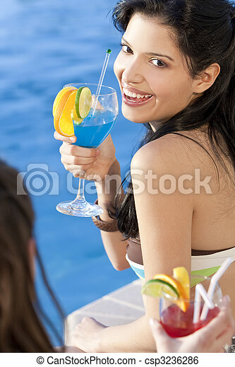 Stunningly beautiful young latina Hispanic woman laughing and  drinking a cocktail by a blue swimming pool with her friend in the foreground. - csp3236286