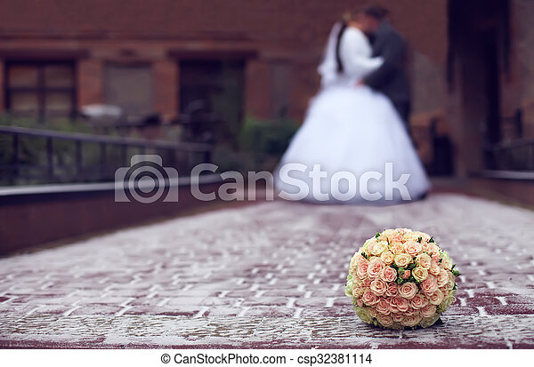 outdoor winter close-up of wedding bouquet lying on snow on a bride and groom kiss background