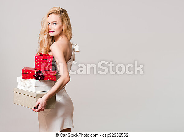 Portrait of a gorgeous young blond woman with Christmas gift boxes.