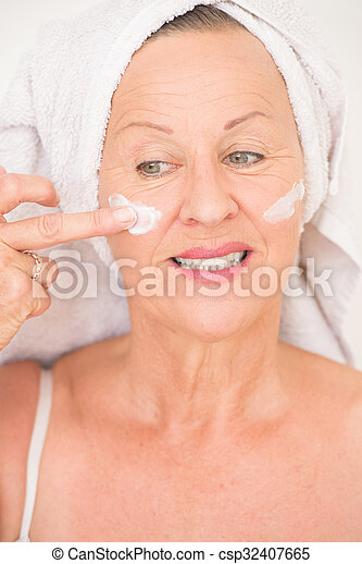 Portrait attractive senior woman with towel and protective skin care creme and moisturiser lotion on happy smiling face, bright background.