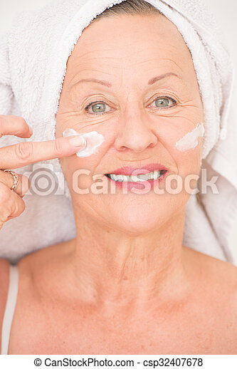 Portrait happy attractive mature woman with towel and protective skin care creme and moisturiser lotion on happy smiling face, bright background.
