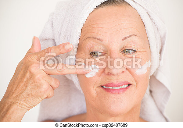 Portrait smiling attractive mature woman with towel and protective skin care creme and moisturiser lotion on happy face, bright background.