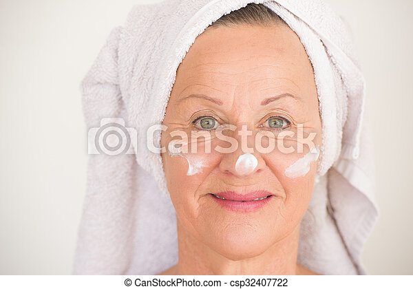 Portrait beautiful mature woman with towel and protective skin care creme and moisturiser lotion on happy smiling face, bright background.